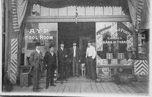 Men in doorway of Rainier Valley Barber Shop and AYP Pool Room, Seattle, 1909