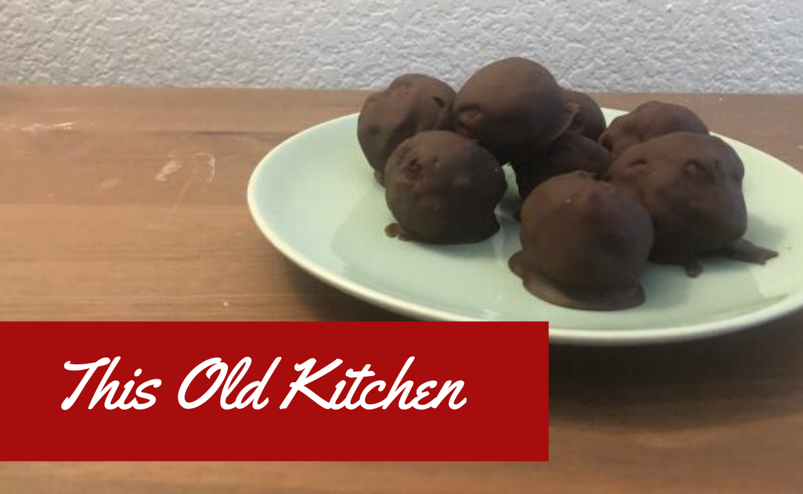 Photo of red velvet cake truffles enveloped in milk chocolate. The title This Old Kitchen is written in the bottom lefthand corner